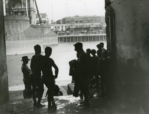 Teenage swimmers by the Thames at Tower Bridge. Image courtesy of the Tower Hamlets Local History Library and Archives.