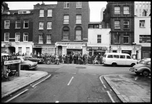 People queuing down the street on Sunday 13th March 1977 before the door opened for the second Half Moon print auction and photo jumble sale. Photo by Mike Goldwater. From the Mike Goldwater Collection at the Four Corners Archive.