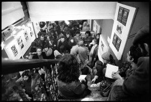 People queuing in the gallery and down the street on Sunday 13 March 1977 before the door opened for the second Half Moon print auction and photo jumble sale. Photo by Mike Goldwater. From the Mike Goldwater Collection at the Four Corners Archive.
